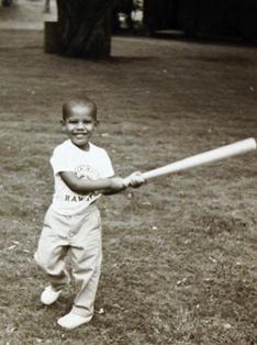 Obama cilik sedang memegang pemukul baseball.